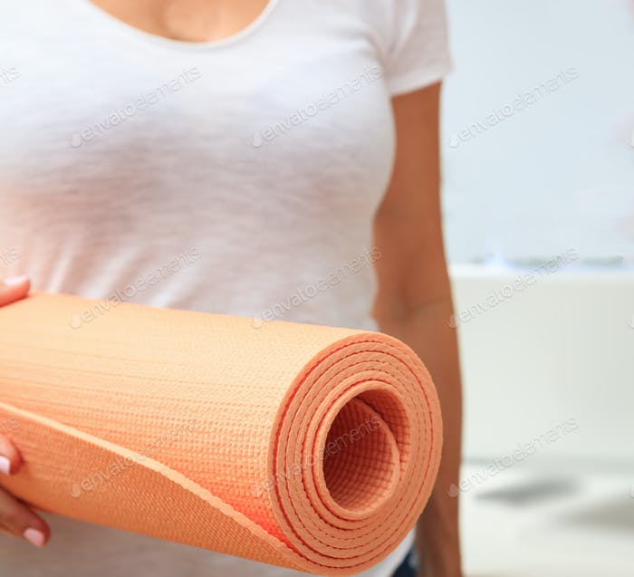 Woman holding an exercise mat, blur white background