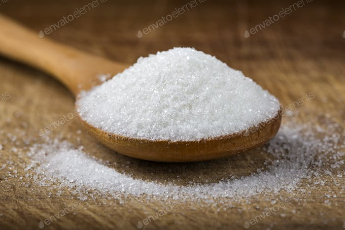 bamboo spoon filled with white sugar over wooden background