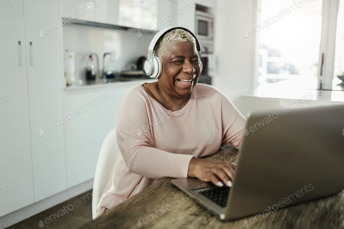 Senior woman using laptop at home - Focus on face