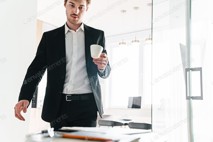 Foto von ernsthaften Brünette Geschäftsmann Kaffee trinken