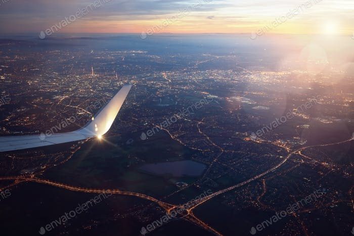 View from landing airplane window of city at sunset
