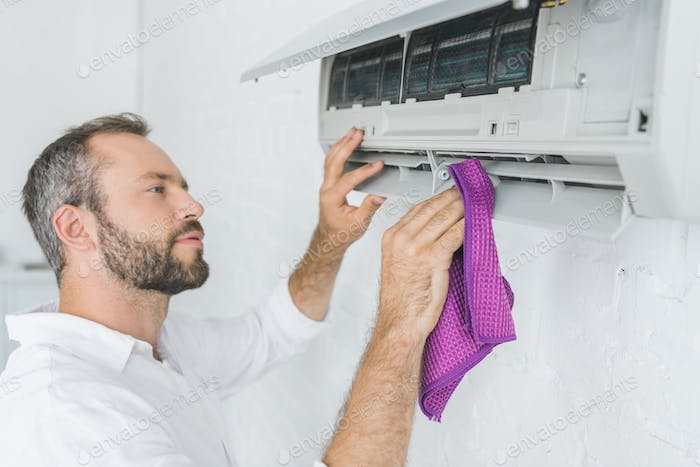 bearded man cleaning air conditioner with rag