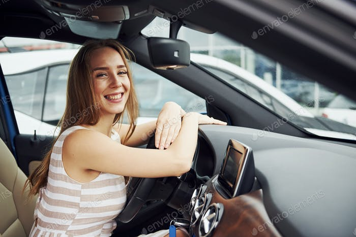 Leans on the steering wheel and smiling. Female driver inside of modern automobile