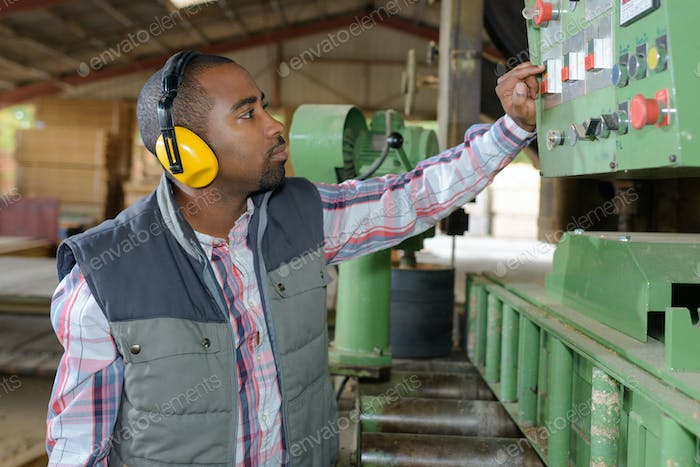 Man pressing buttons on industrial machine