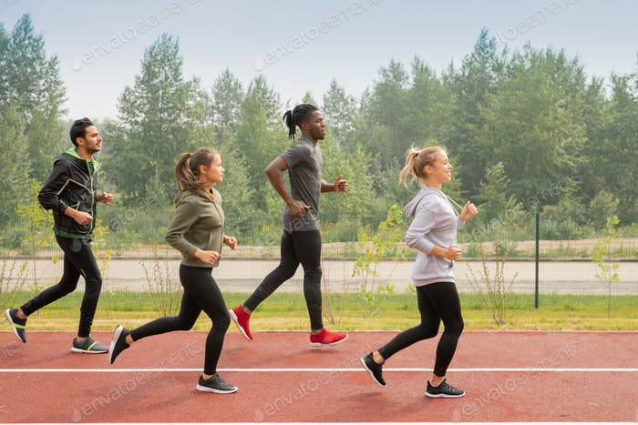 Side view of four young sportsmen and sportswomen running down racetracks