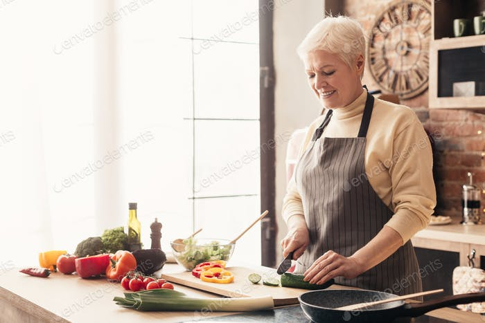 Caring grandmother preparing healthy lunch for family