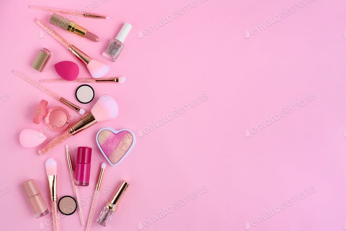 Makeup brushes and decorative cosmetics on pink background, with empty space for text. Top view