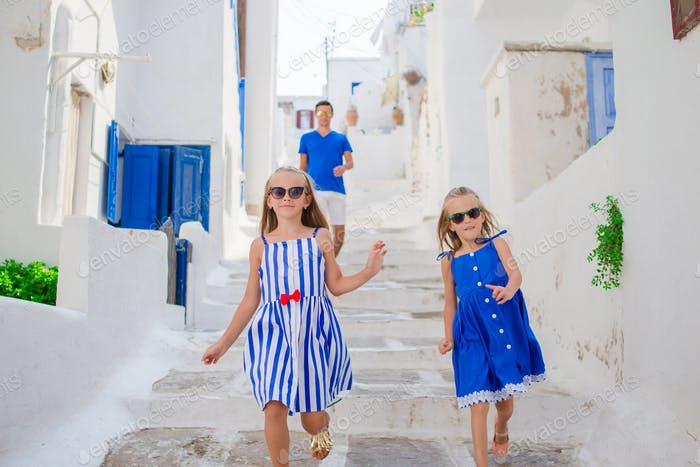 Family vacation in Europe. Father and kids at narrow street on Mykonos Island, in Greece