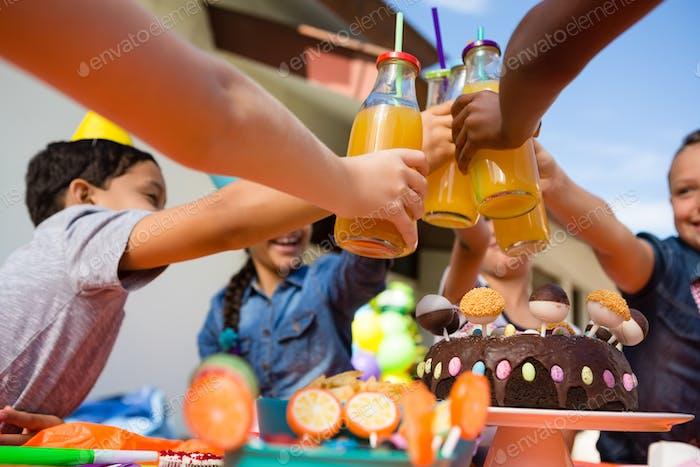 Close up of children toasting juice