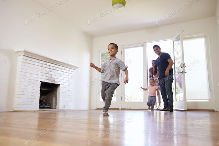 Aufgeregte Familie Erkunden Sie neues Zuhause am Umzugstag