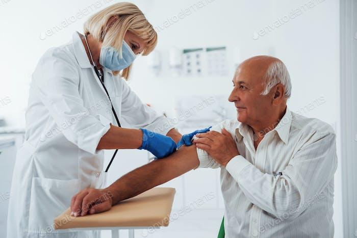 Ärztin injiziert ältere männliche Patientin mit Spritze in der Klinik