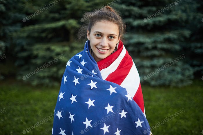 Smiling student girl wrapped in big national flag