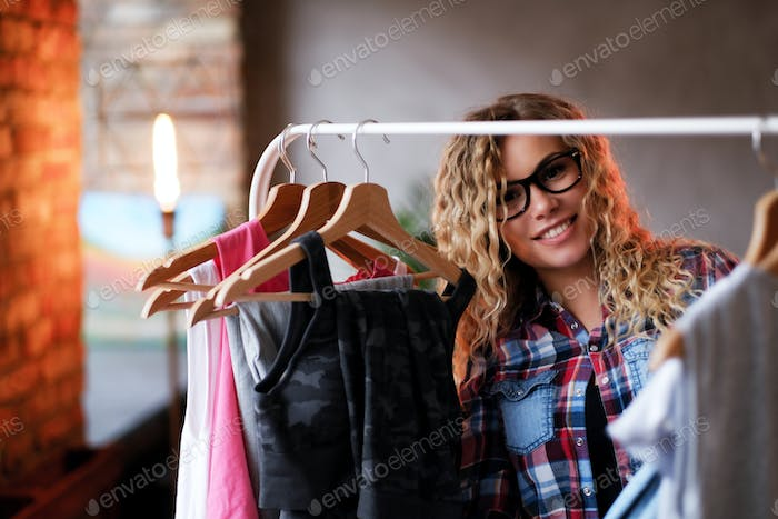 Smiling happy woman in glasses and checkered shirt chooses clothes for her holidays.