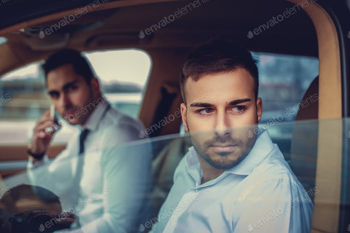 Two men in a white shirts in a car.