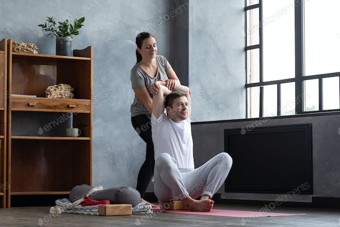 Man doing shoulders stretching. Female teacher helping him to stretch muscles.