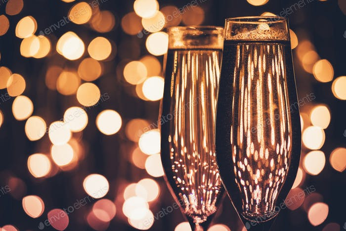 close up view of glasses of champagne against festive lights