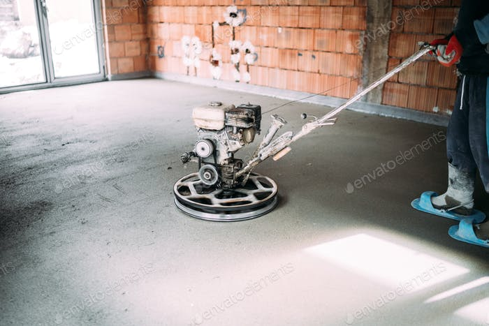 industrial worker finishes concrete screed with trowel machine