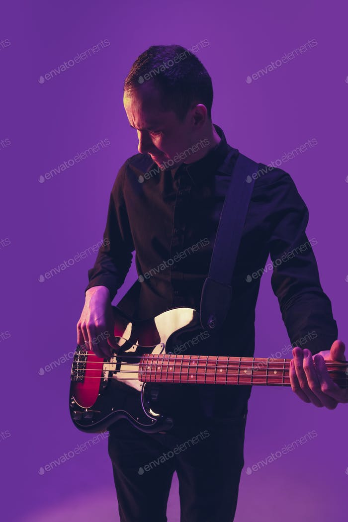Young caucasian musician playing guitar in neon light on purple background