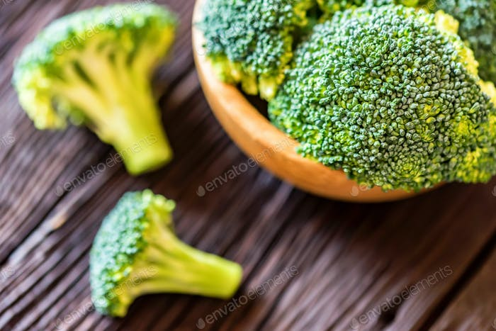 Fresh broccoli in wooden bowl on wooden surface