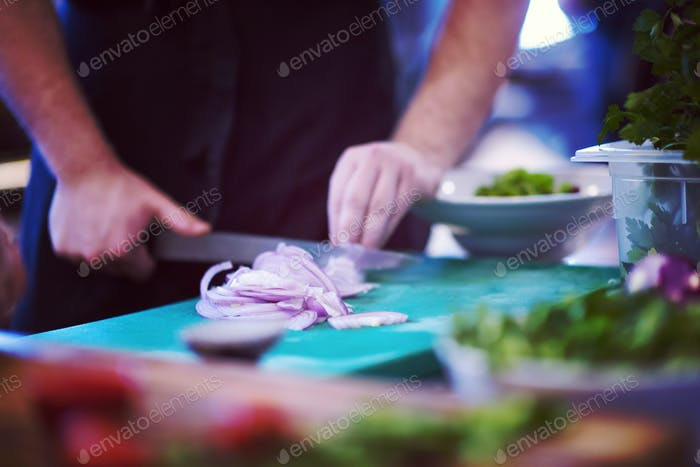 Chef  hands cutting the onion with knife