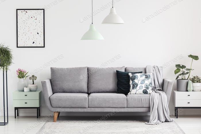 Graues Sofa zwischen Schränken mit Pflanzen in weißen Wohnzimmer inte