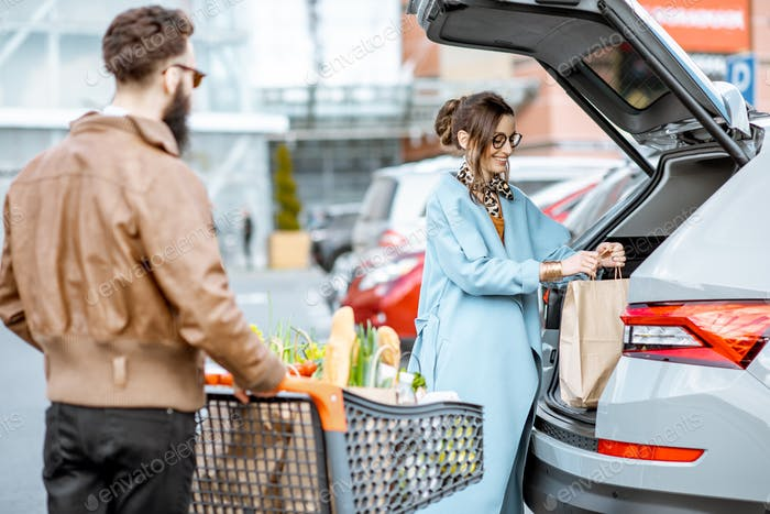 Man and woman with fresh food on the supermarket parking