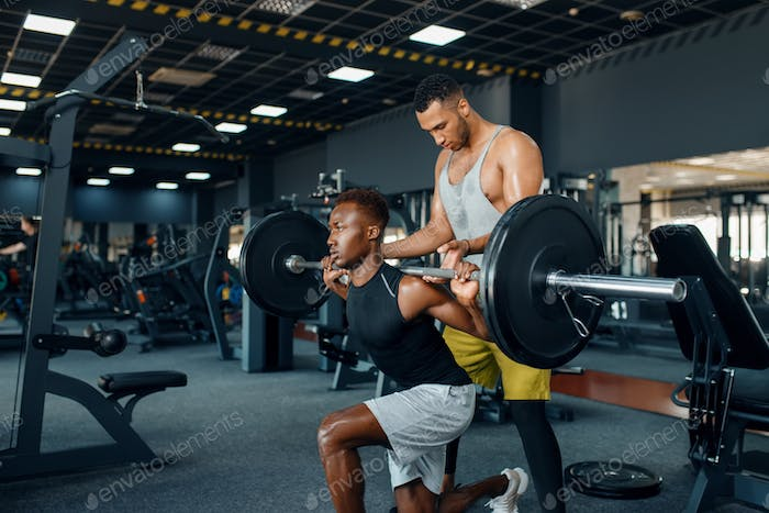 Trainer helps the athlete, exercise in gym