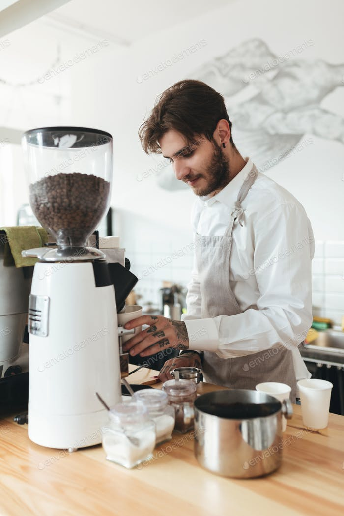 Barista in apron and white shirt making coffee by coffee machine at cafe