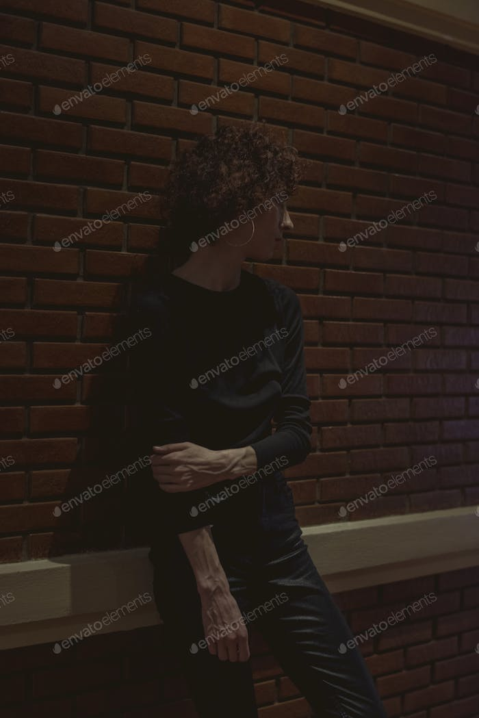 Woman standing by a brick wall