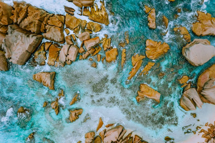 Aerial top view of tropical coastline. Bizarre granite rocks boulders, turquoise azure water