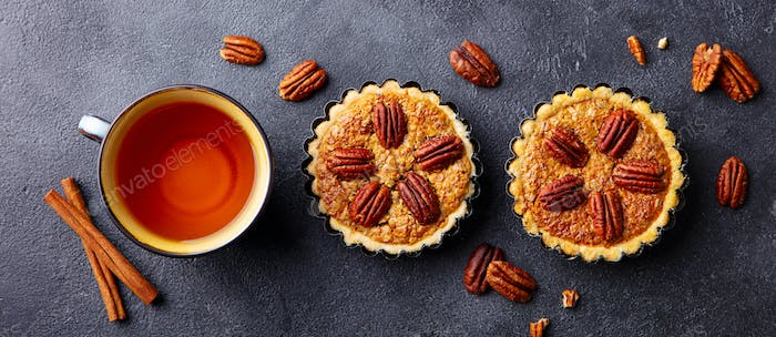 Pecan Pies, Mini Tarts with Cup of Tea. Dark Background. Close up. Top View.