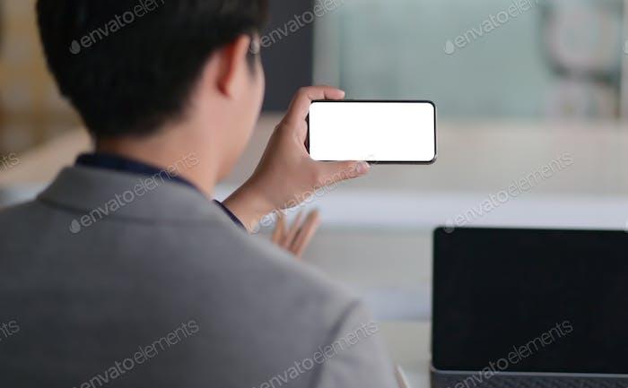 Geschnitten Schuss von Ein junger Geschäftsmann Online-Meeting mit einem Smartphone, Er arbeitet von zu Hause aus.