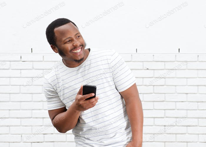 cool black guy smiling with cellphone against white wall