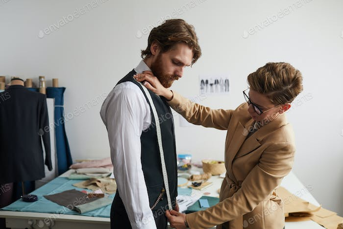 Designer sewing the suit for businessman