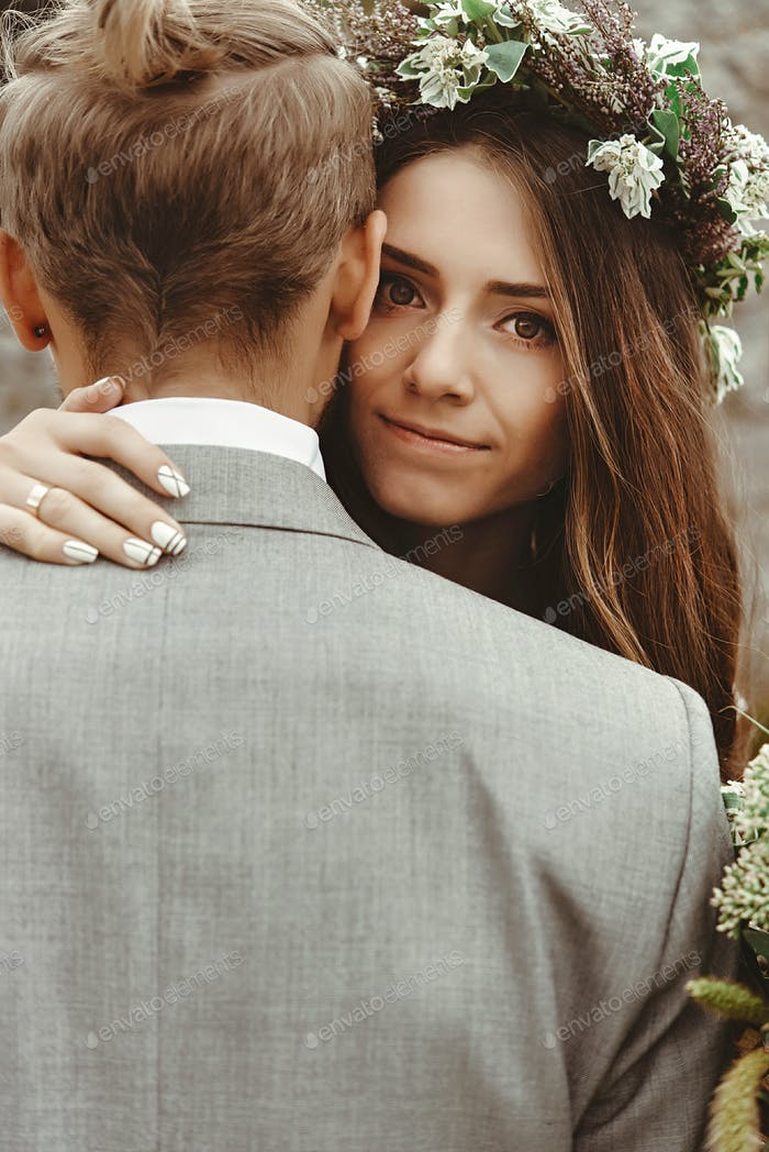 gorgeous bride and stylish groom hugging with emotions,  boho wedding couple