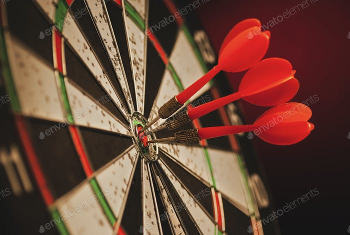 Three darts in the center bulls eye of a target