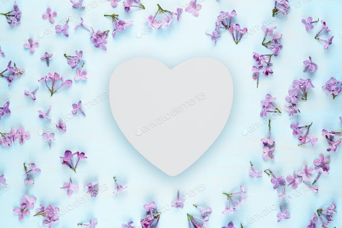 Blank white wooden heart and lilac flowers on blue background