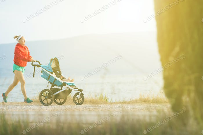 Running mother with baby stroller enjoying sunset landscape