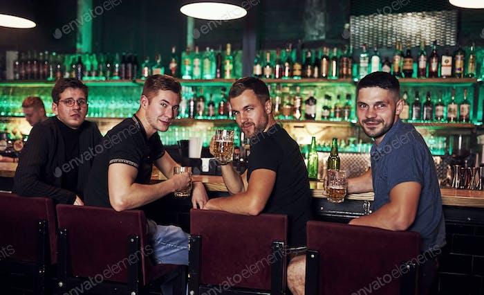 Freunde ruhen in der Kneipe mit Bier in den Händen. Konversation haben
