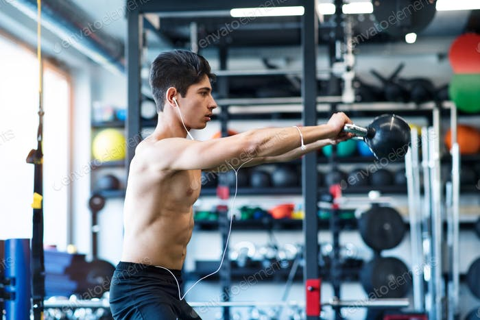 Young fit hispanic man in gym doing kettlebell swings