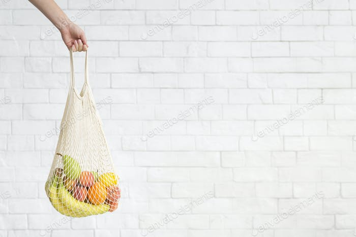 Woman carrying Healthy products composition in reusable net bag