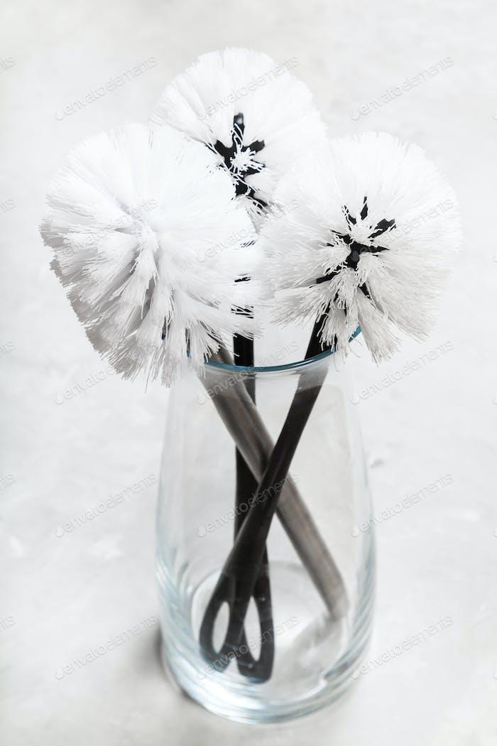 toilet brushes in glass vase on concrete floor
