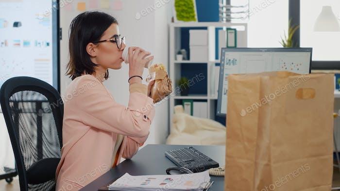 Geschäftsfrau isst etwas leckeres Sandwich trinkt vor dem Monitor Kaffee