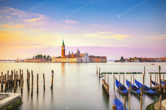 Venice lagoon, San Giorgio church, gondolas and poles. Italy
