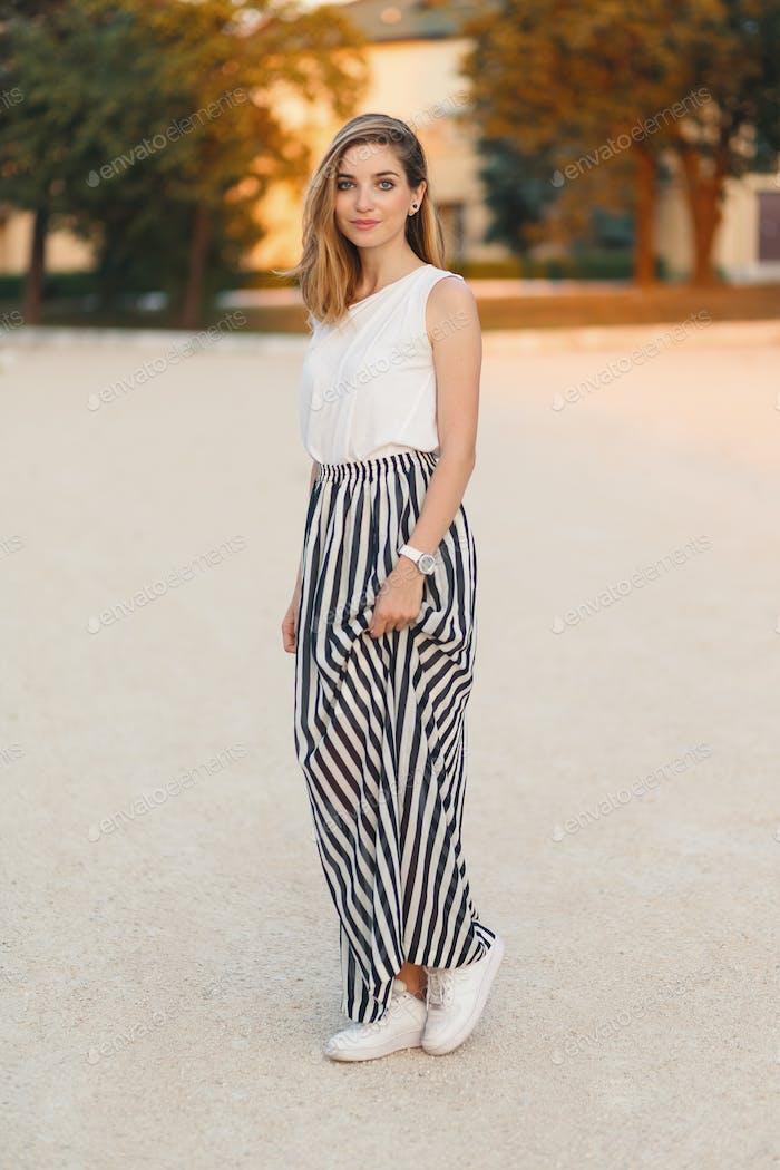 Beautiful, fashionable smiling girl posing in a stylish, feminine skirt.