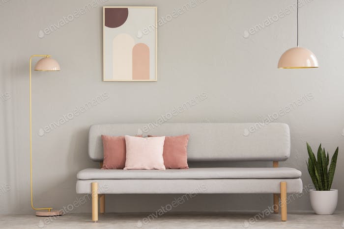Real photo of grey sitting room interior with couch with cushion