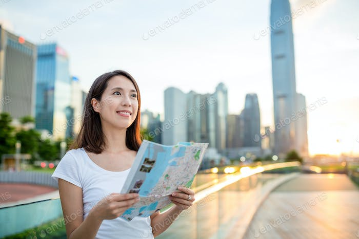 Woman using city map in Hong Kong city during sunset