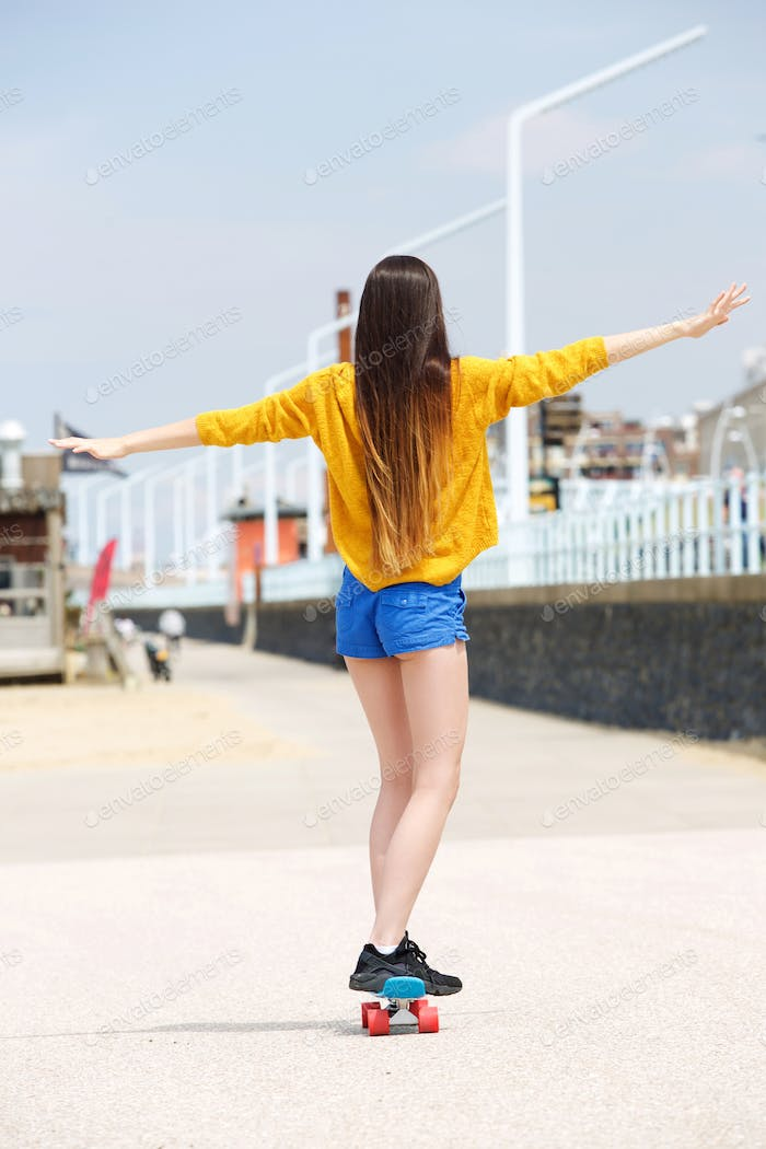 Woman balancing on skateboard outside