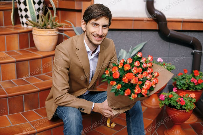 Smiling handsome man holding a bunch of roses