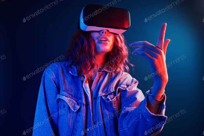 Facial expression of young girl with virtual reality glasses on head in red and blue neon in studio